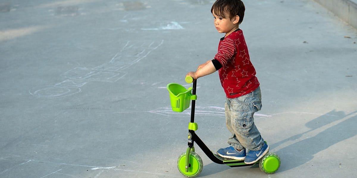 Criança se divertindo com um patinete de 3 rodas